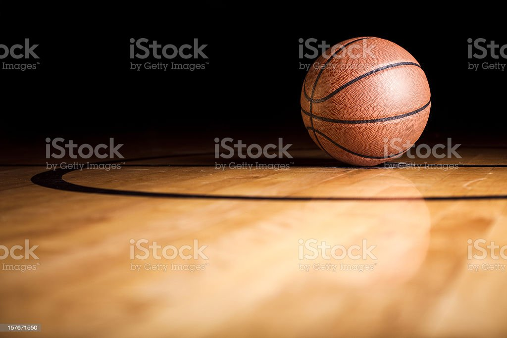 A single basketball sitting on the court stock photo