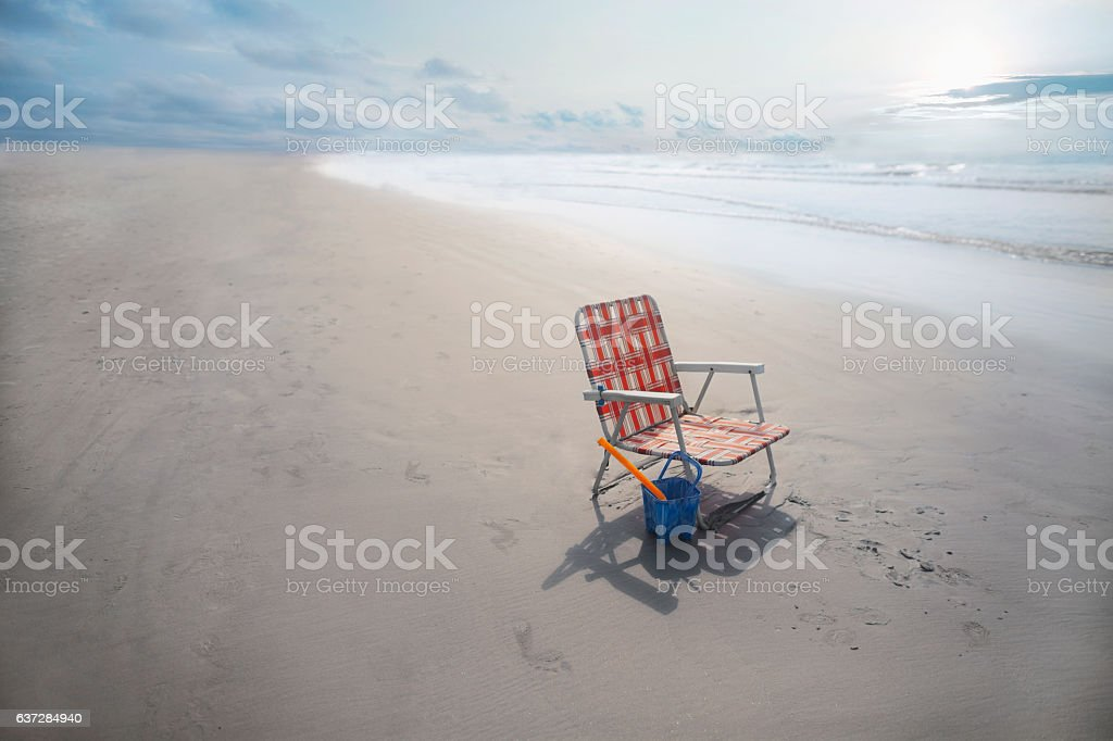 Single beach chair with bucket and shovel on the shore stock photo