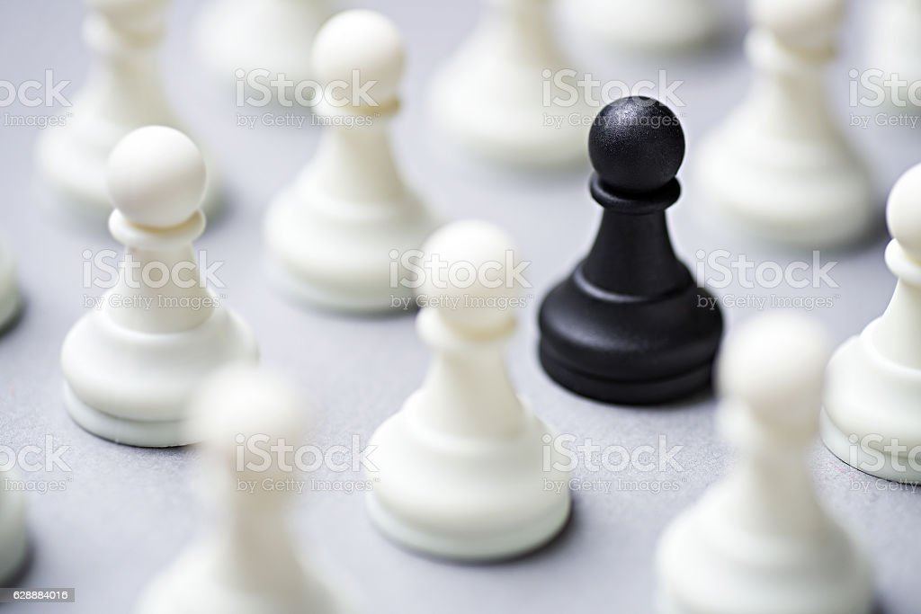 Single black chess piece amongst white ones stock photo