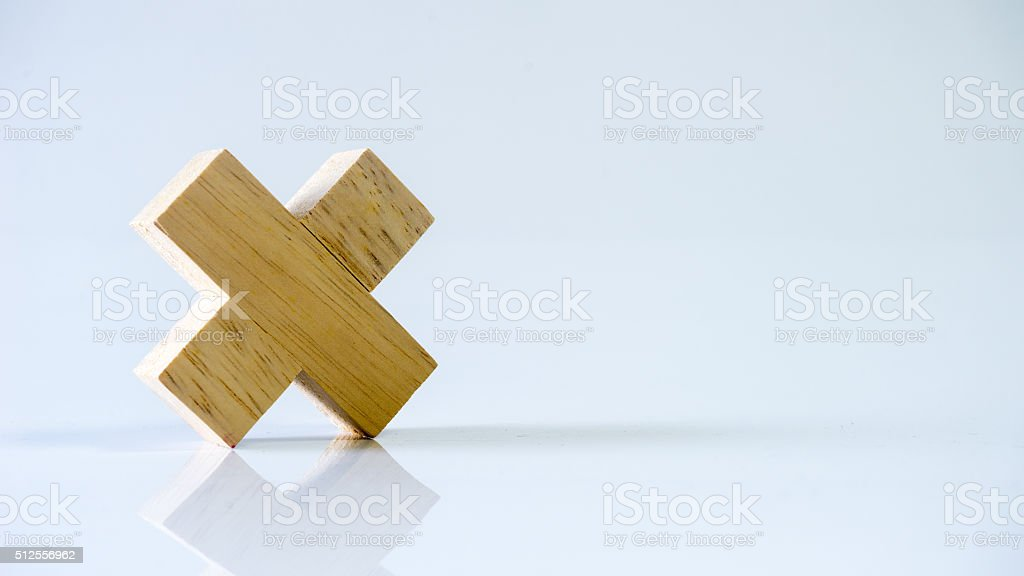 Single block wooden letter X or multiplication sign symbol stock photo