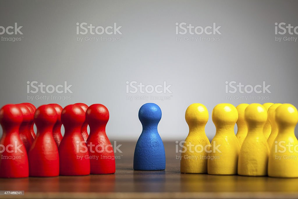 Single blue pawn figure between red and yellow groups stock photo