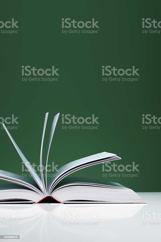 Single book, opened over green background royalty-free stock photo