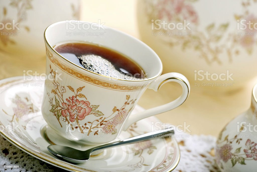 A single, classic cup of tea with a spoon on the side royalty-free stock photo