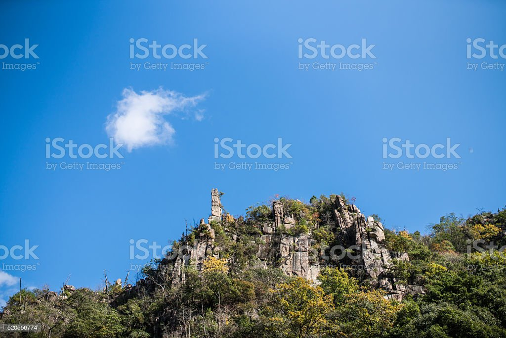 Single cloud in a blue sky above rocky hill stock photo