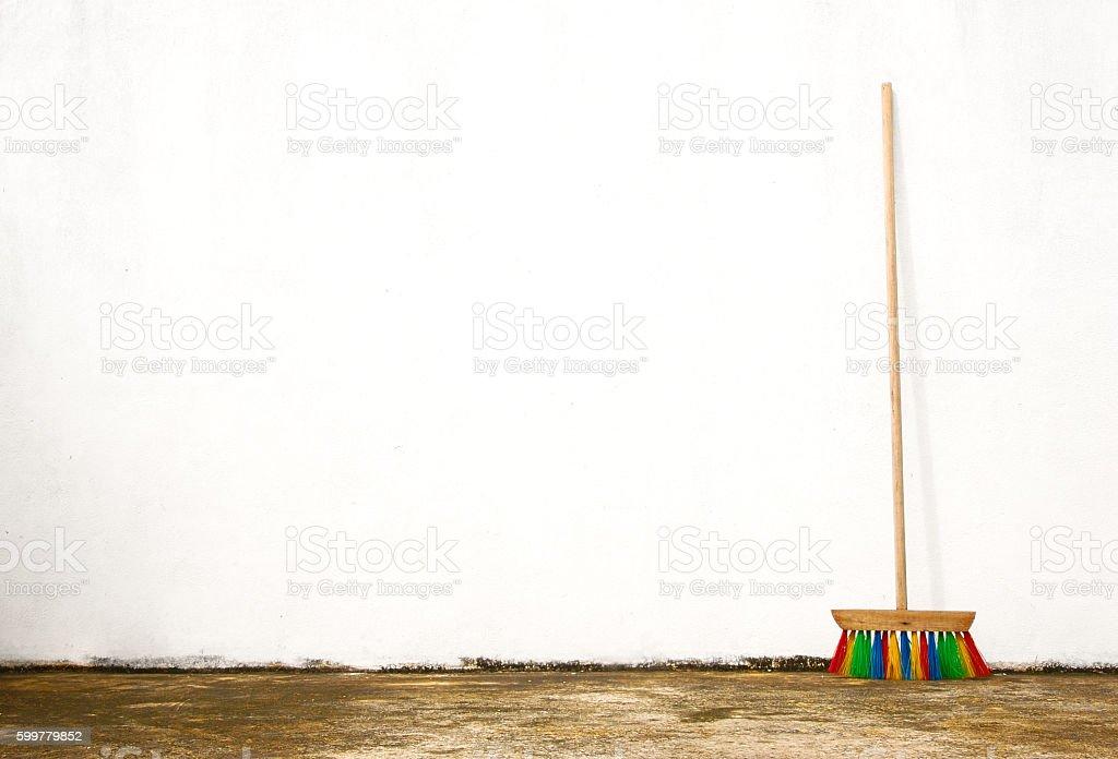 Single colorful broom outdoors against a white wall foto de stock libre de derechos
