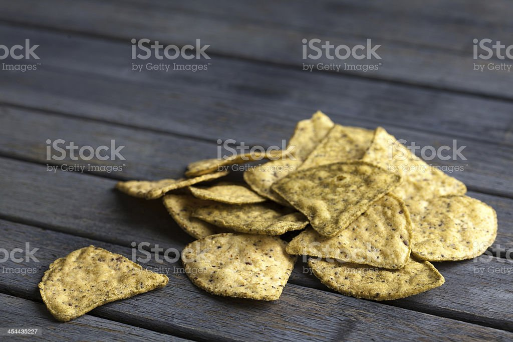 single corn chip next to a pile of chips royalty-free stock photo