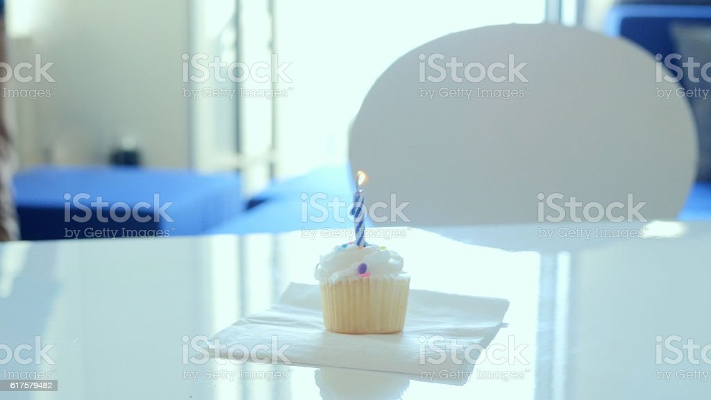 Single cupcake with candle on table stock photo