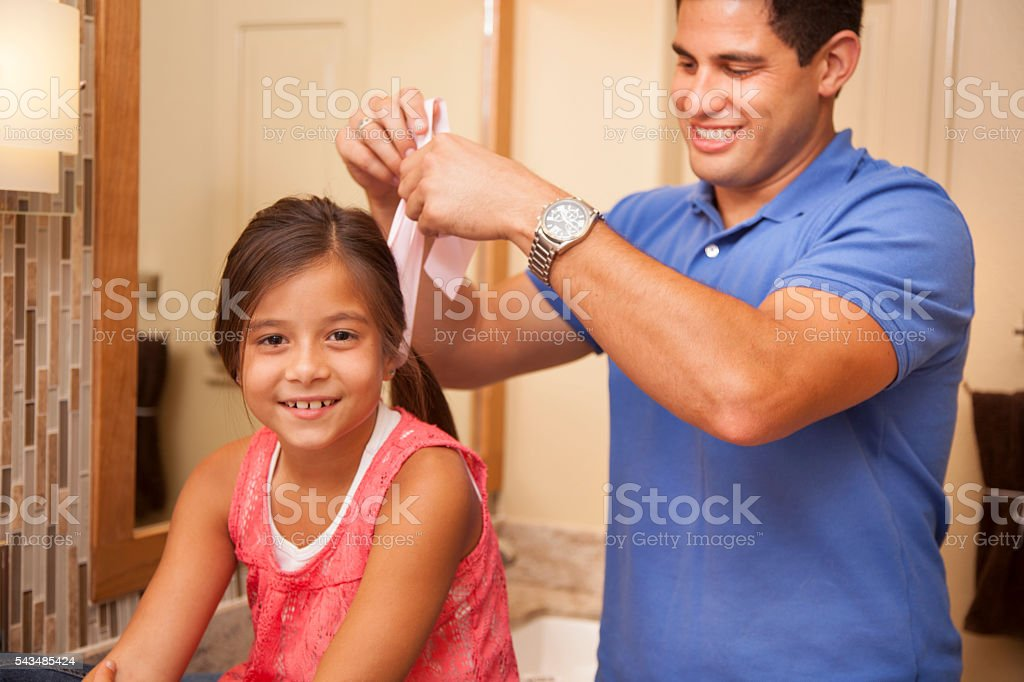 Single dad adds a bow to daughter's hair in bathroom. stock photo