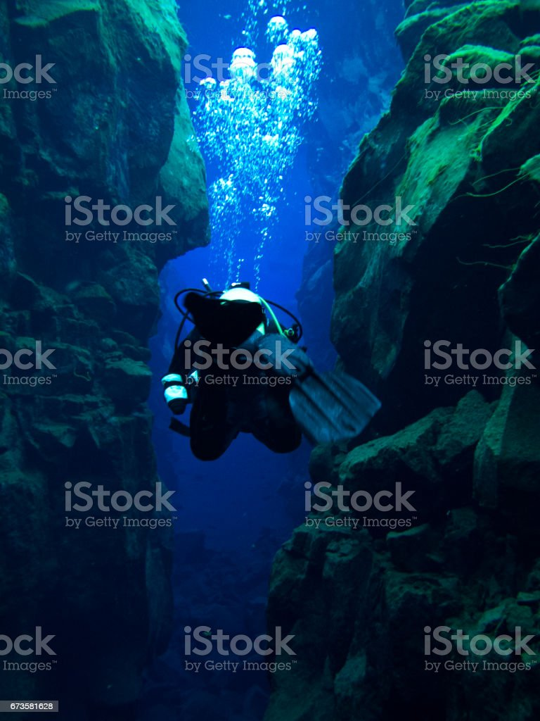 Single Diver Action Shot Swimming Through Continental Split at Silfra in Deep Section at Pingvellir National Park with Bubbles stock photo
