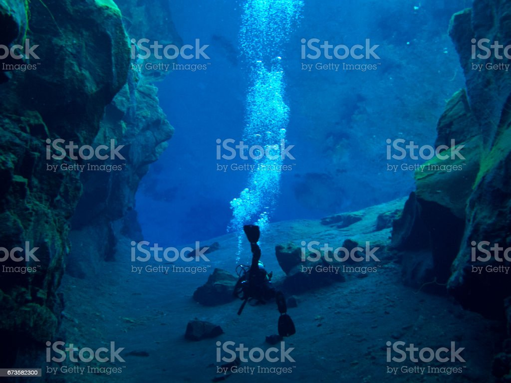 Single Diver at Sandy Bottom of Continental Split at Silfra in Deep Section at Pingvellir National Park with Lots of Bubbles stock photo