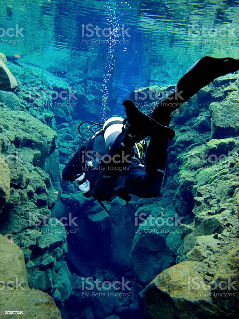 Single Diver Swimming Through Continental Split at Silfra in Deep Section at Pingvellir National Park stock photo