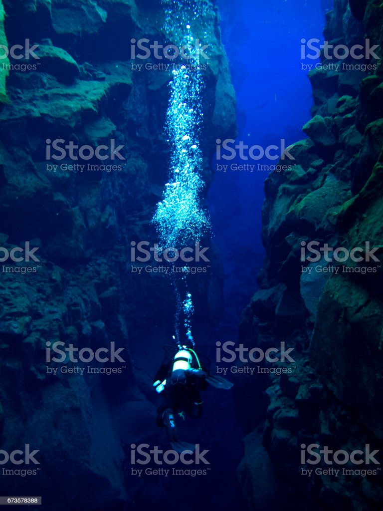 Single Diver with Bubbles Between Large Rock Formations at Continental Split at Silfra in Deep Section at Pingvellir National Park stock photo