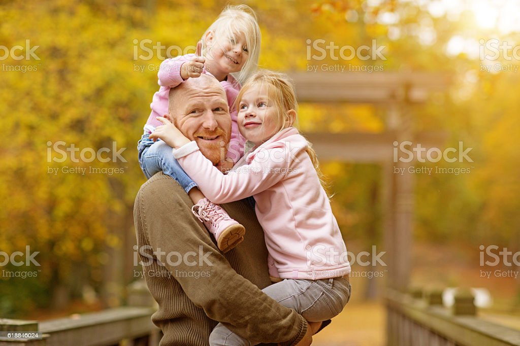 Single father and daughters posing together in autumnal park surroundings stock photo