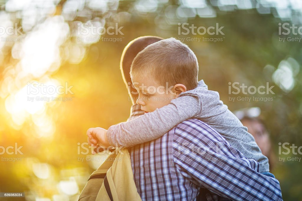 Young father and his son hugging in the park,sideview