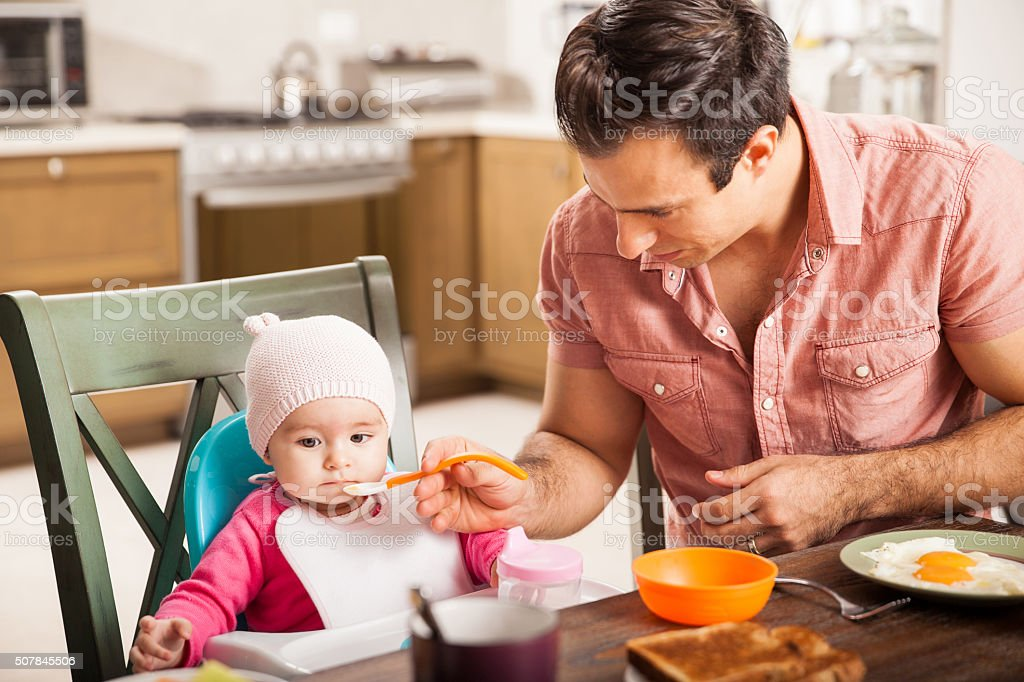 Single father feeding his baby daughter at home stock photo