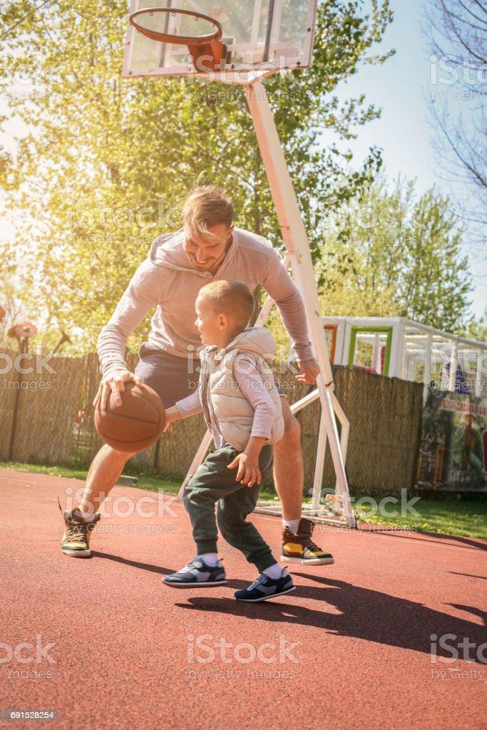 Single father playing basketball together on the basketball court.