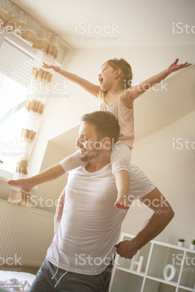 Single father spending time with his daughter. Little girl sitting on...