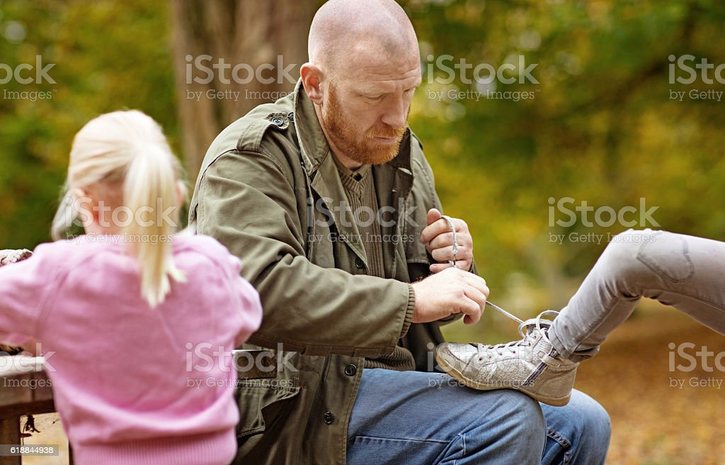 Single father tying blonde daughter's shoelace in autumnal surroundings stock photo