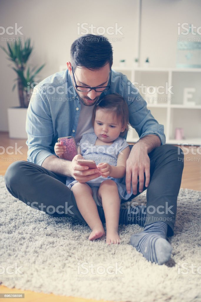 Single father wit his daughter using smart phone. Father and little...