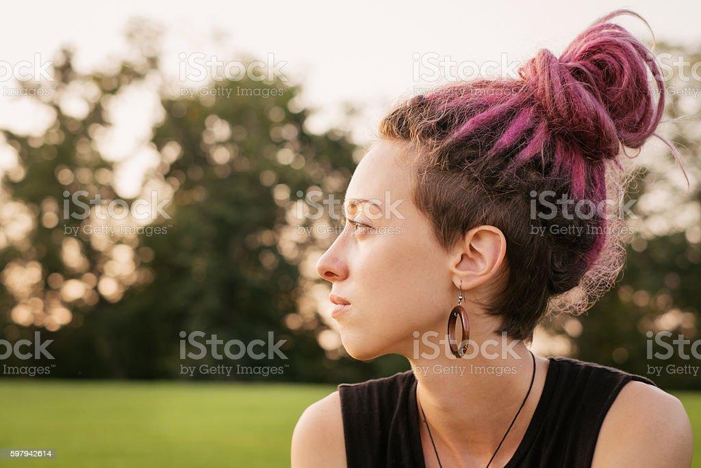 Single female sitting sad outdoors. stock photo