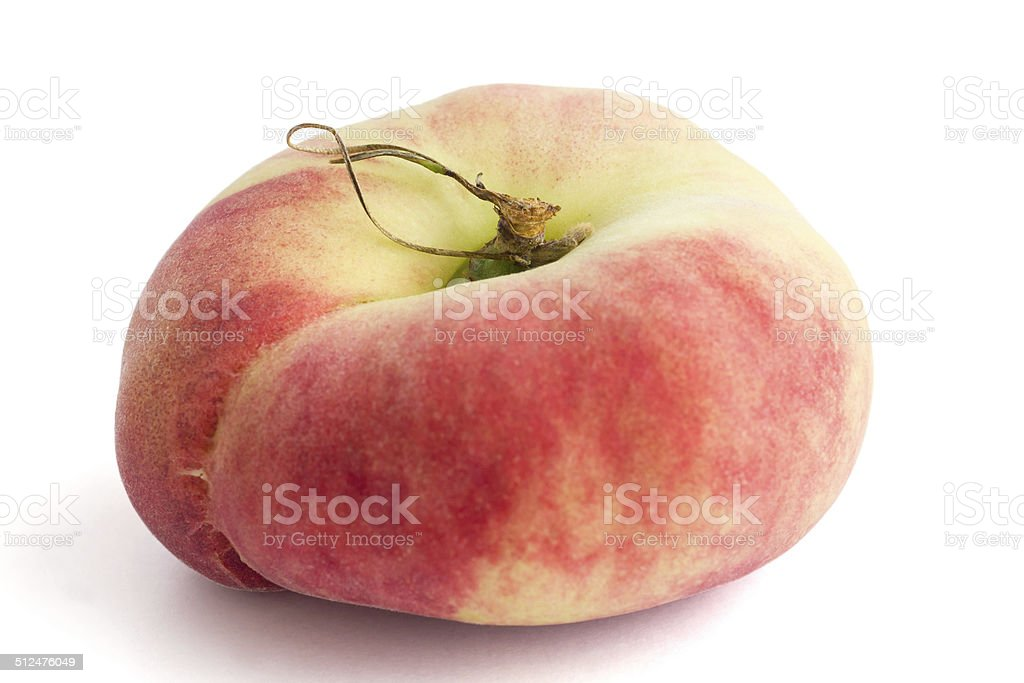 Single flat peach on white with selective focus. stock photo