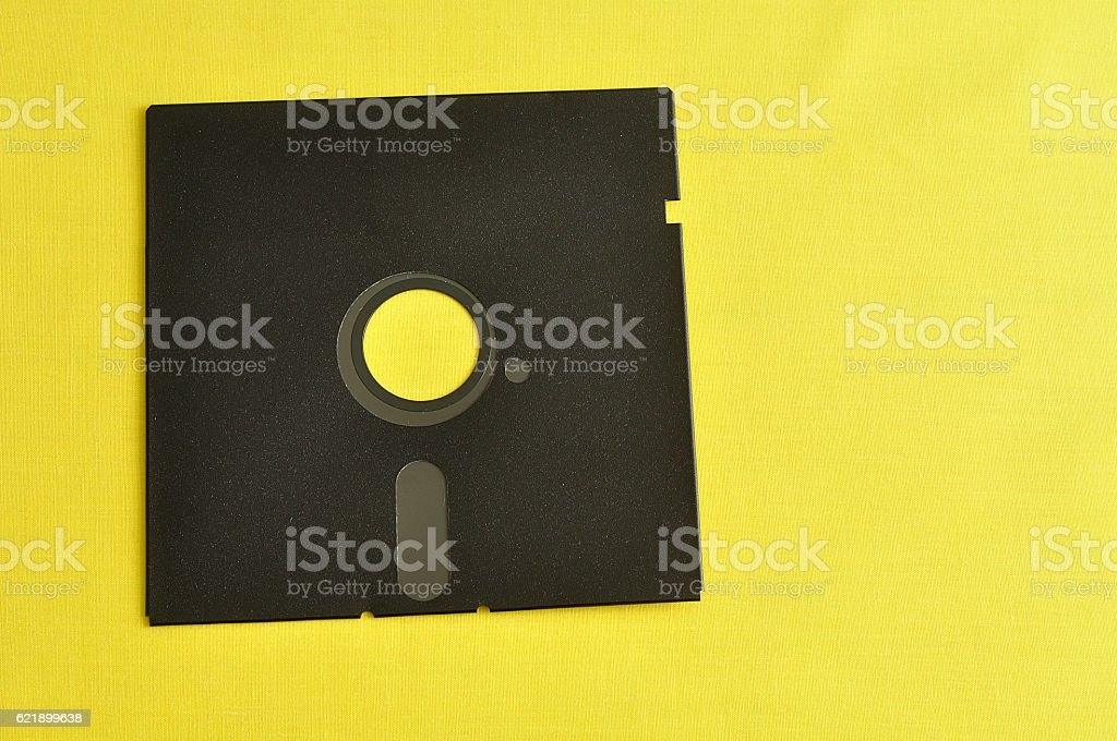 Single floppy disc isolated on yellow background stock photo