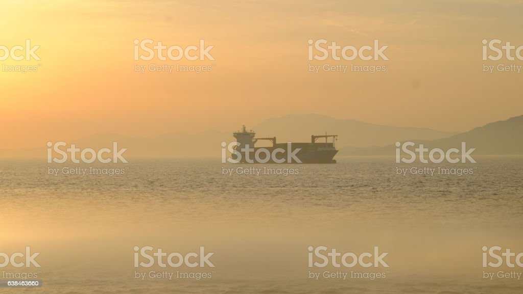 Single freight ship around Athens at sunset stock photo