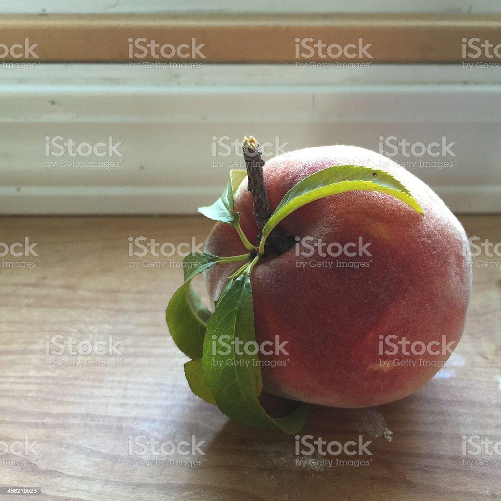 single fresh peach on wood countertop stock photo