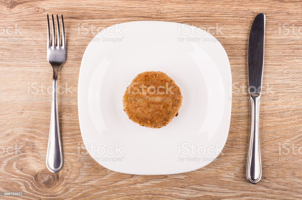 Single fried cutlet in white plate, fork and knife stock photo