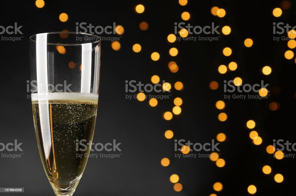 Single glass of Champagne, black background, defocused yellow, orange lights royalty-free stock photo