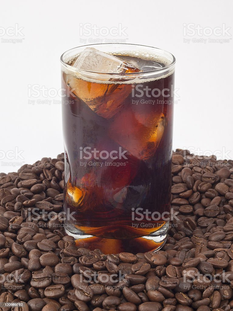 A single glass of iced coffee on a pile of coffee beans stock photo