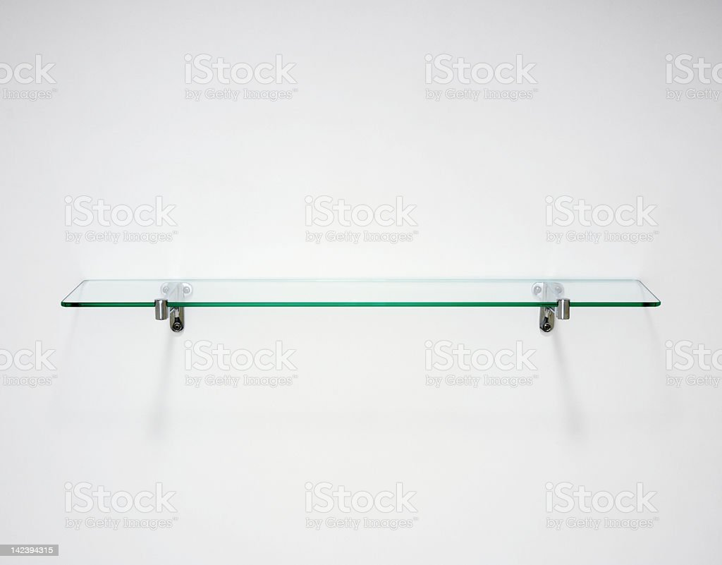 Single glass shelf with blue tint on white wall royalty-free stock photo