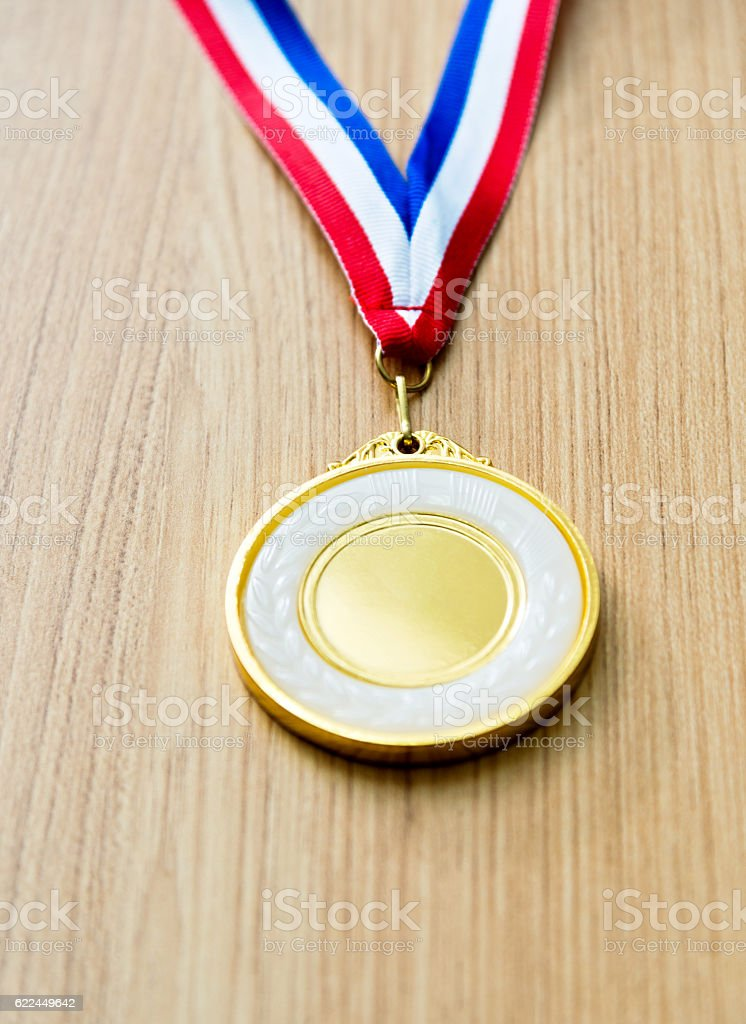 Single gold medal on wood desk stock photo