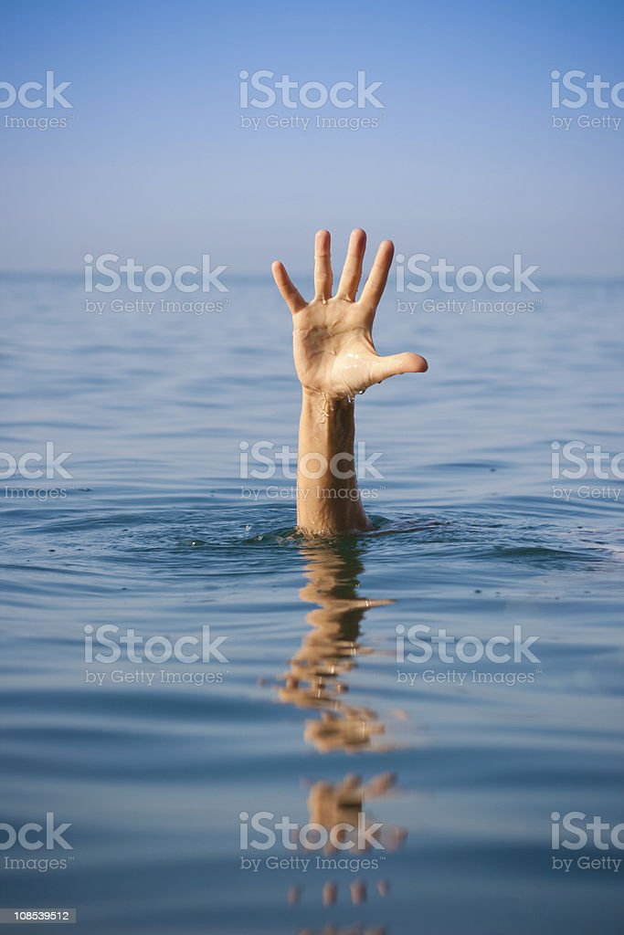 single hand of drowning man in sea asking for help stock photo