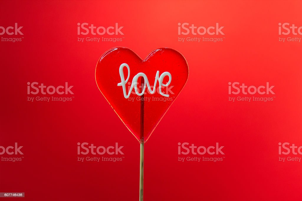 Single heart-shaped Lollipop with love sign on red background stock photo