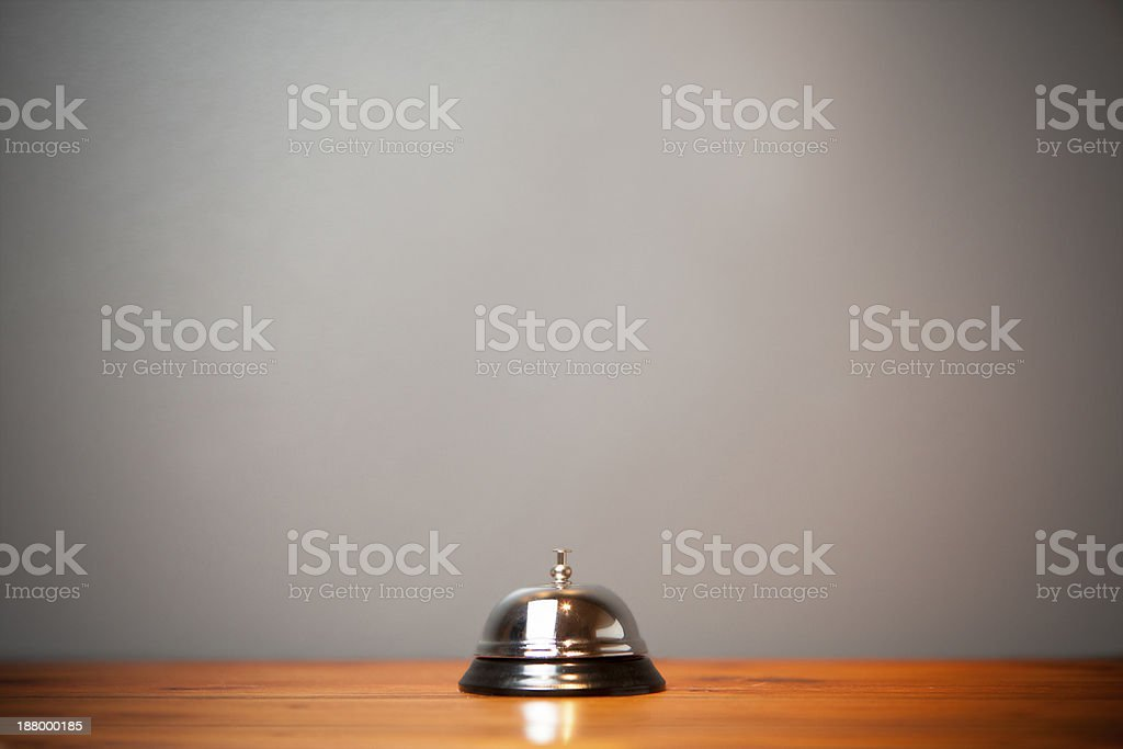 A single hotel bell placed on a wide desk top royalty-free stock photo