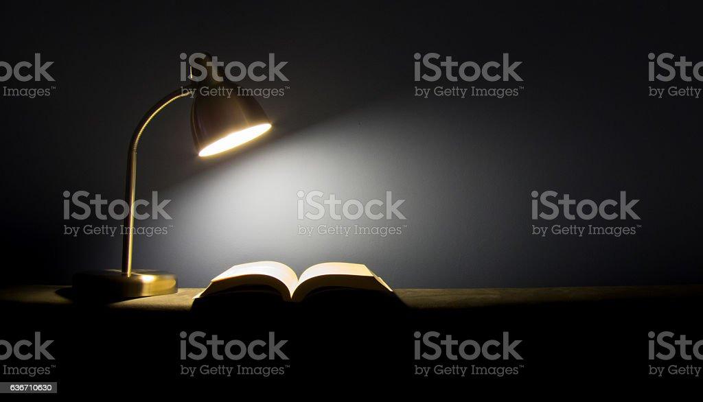 Single lamp illuminating a book in the dark stock photo