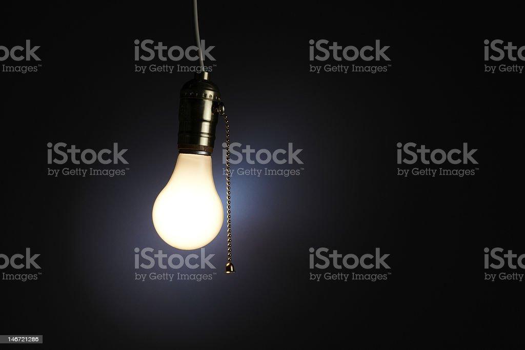 Single lit light bulb on a chain on a black background stock photo