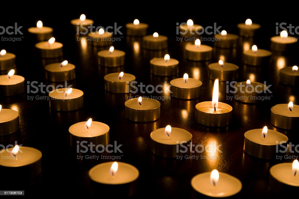 Single lit tealight candle surrounded by others with smaller flames stock photo