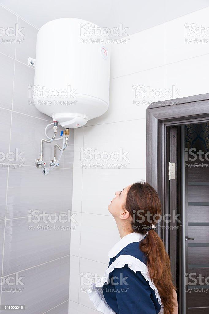 Single maid inspecting water tank stock photo