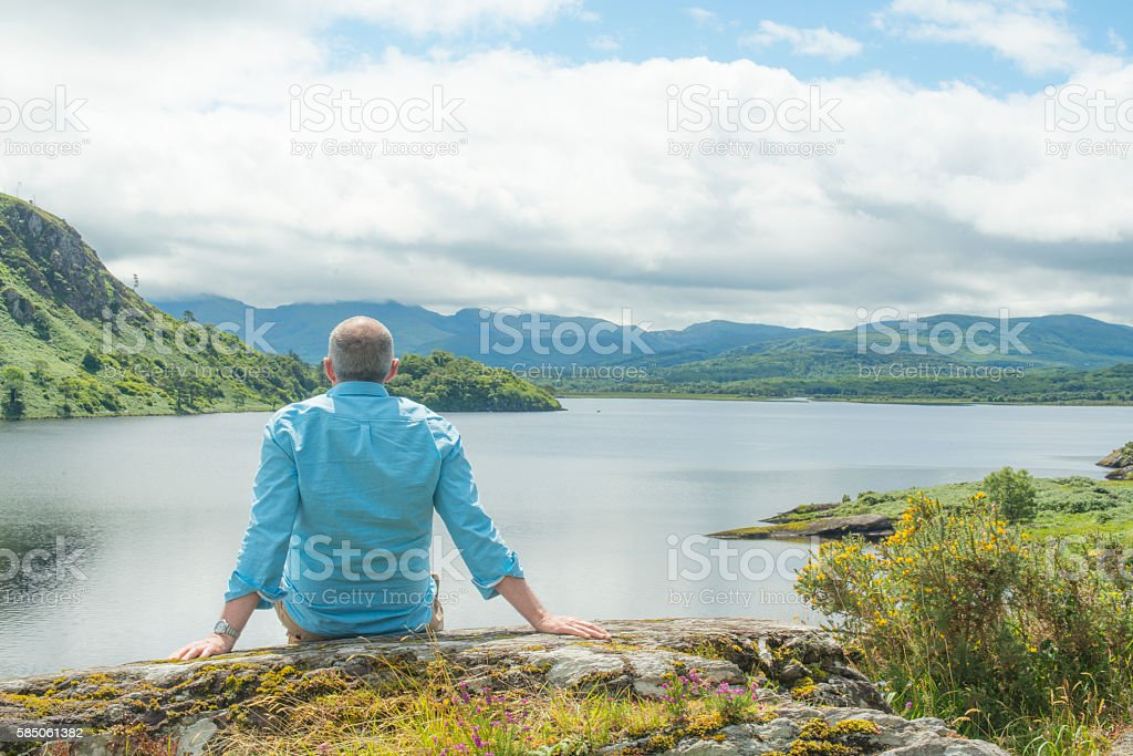 Single man relaxing on a rock in Kerry, Ireland. stock photo