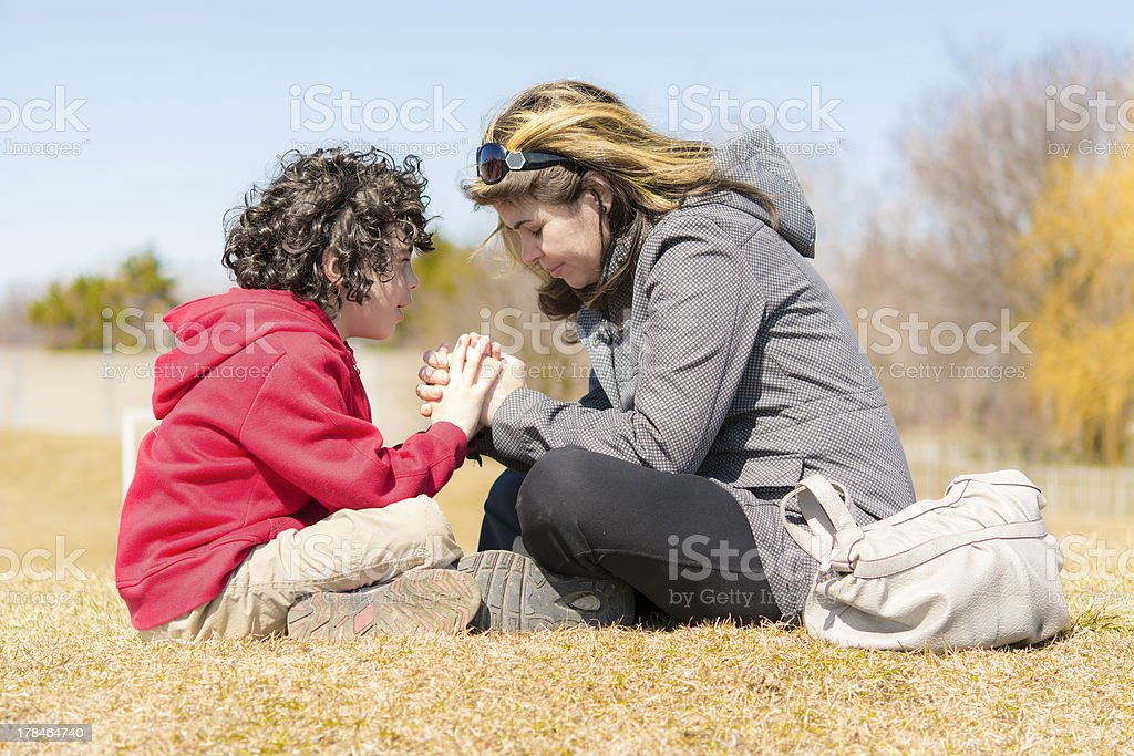 Single Mother and Son Praying Outdoors stock photo
