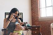 Single mother multitasking on the phone while feeding baby