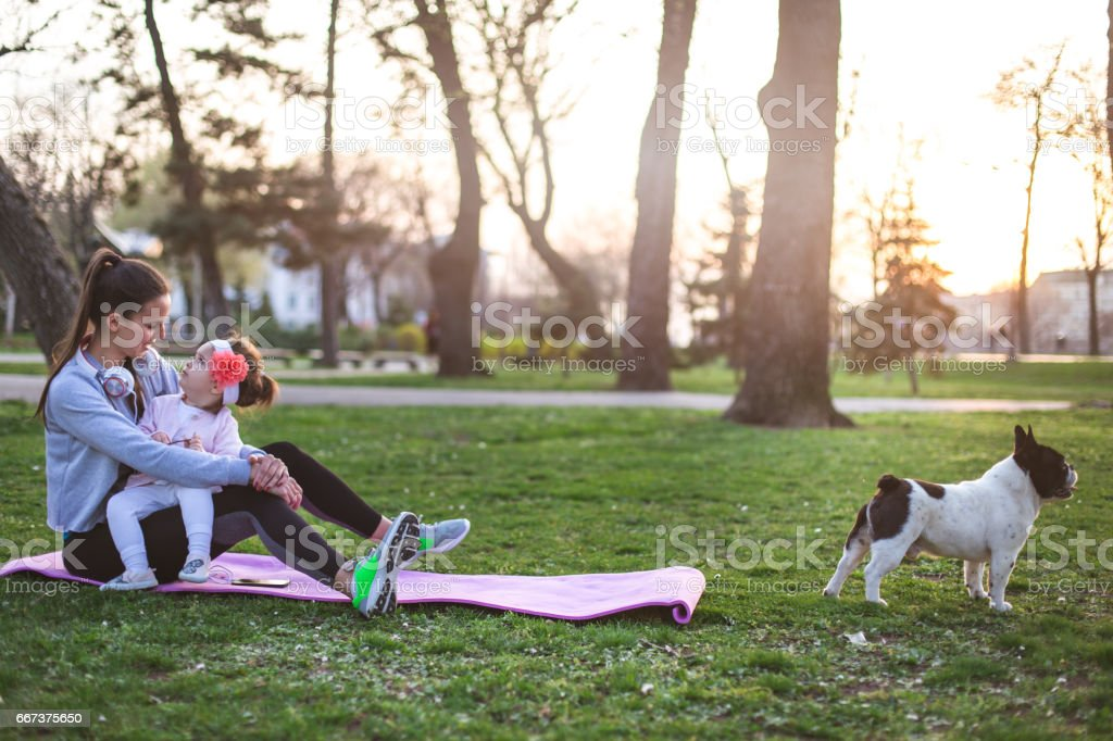 Single mother with cute baby girl on exercise mat bonding stock photo