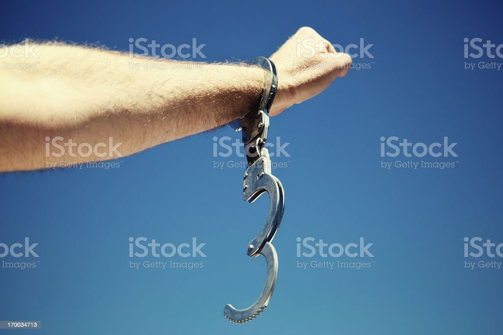 Single open handcuff on male arm symbolizing freedom stock photo