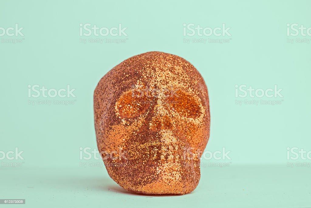 Single Orange Halloween Skull on Green Background stock photo