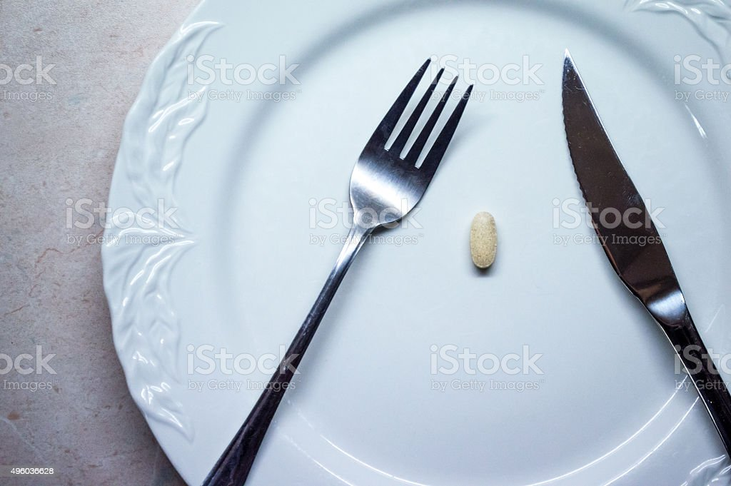 Single Pill/Tablet on a White Dinner Plate Overhead View royalty-free stock photo