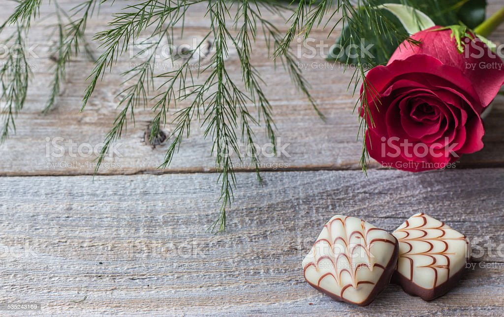 single pink rose with two chocolates on old wood background stock photo