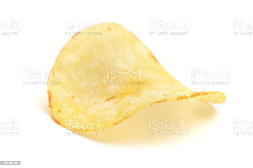 A single potato chip against a white background stock photo