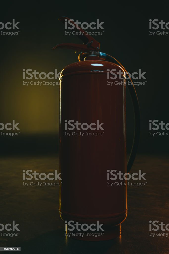 single protective metal fire extinguisher standing on the floor stock photo